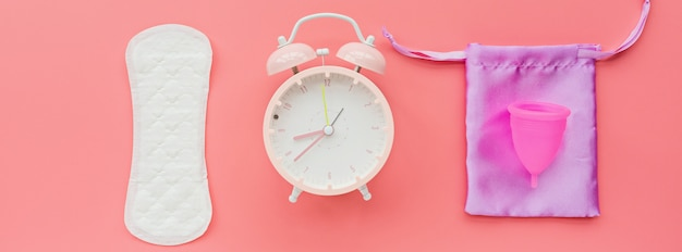 Menstrual cup with bag, hygienic pad, alarm clock on pink background.