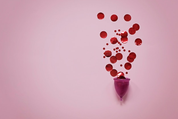 Menstrual cup with red particles on pink surface