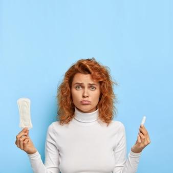 생리주기 및 여성 건강 개념. 불만족 된 여자는 위생 면화 패드와 탐폰을 보유