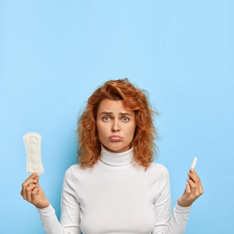 Menstrual cycle and women health concept. dissatisfied woman holds sanitary cotton pad and tampon
