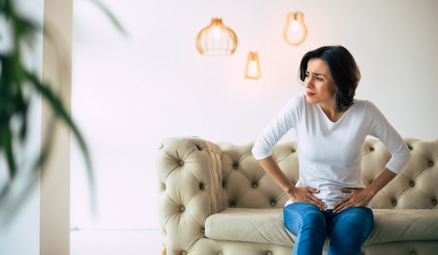 Menstrual disorder. young woman is sitting on a sofa and touching her lower stomach while suffering from period pain.
