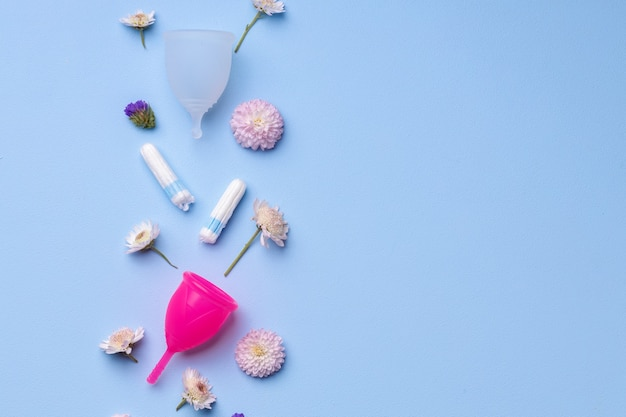 Menstrual hygiene products with flowers on blue surface