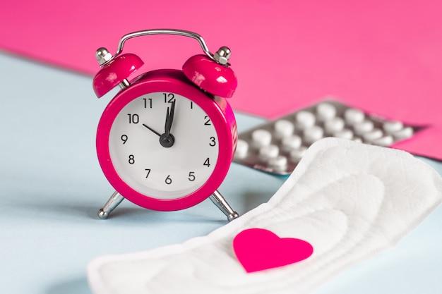 Menstrual pads, alarm clock, hormonal contraceptive pills. menstruation period concept. pain reliever for menstrual pain