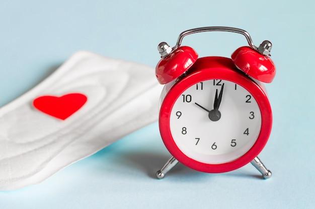 Menstrual pads, alarm clock. menstruation period concept. feminine hygiene products