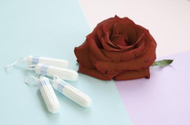 月経パッドとタンポンと赤いバラの花