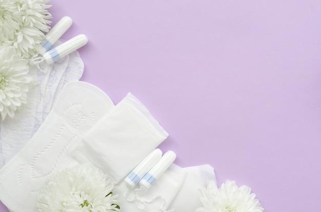柔らかい白い花の生理用ナプキンとタンポン
