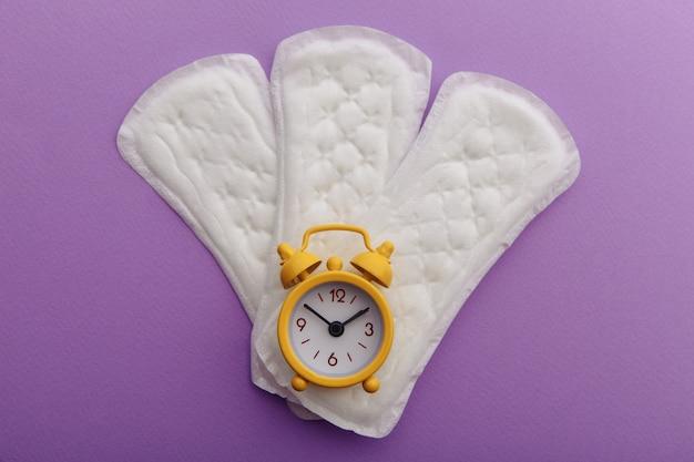 ライラックの背景に月経パッドと黄色の目覚まし時計。女性の月経周期の概念。