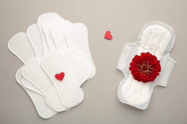 Menstrual pads on a grey background. a rose flower lies on a menstrual pad. menstruation cycle. hygiene and protection. top view.