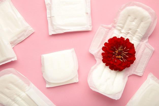 분홍색 배경에 생리대입니다. 장미 꽃은 생리대에 놓여 있습니다. 월경주기. 위생 및 보호. 평면도.