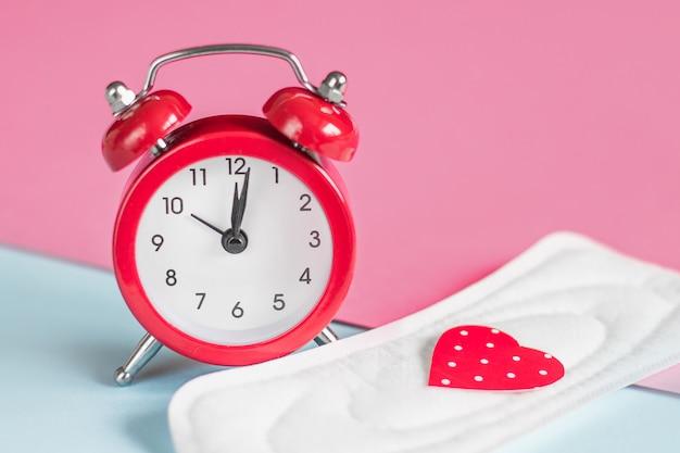 Менструальные прокладки, красный будильник на розовом фоне. концепция менструального периода. концепция задержки менструального цикла