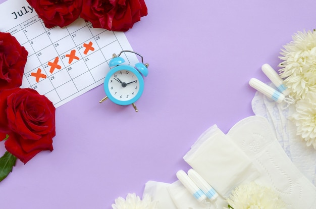 Menstrual pads and tampons on menstruation period calendar with blue alarm clock and red rose flowers