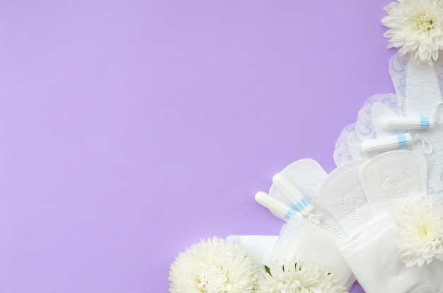 Menstrual pads and tampons with tender white flowers on pastel lilac background