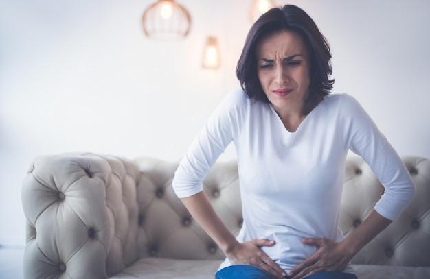 생리통. 슬픈 여인이 소파에 앉아 두 손으로 아랫배를 잡고 생리통을 앓고 있습니다.