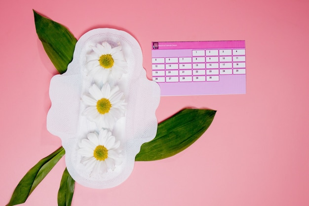 생리 기간 개념입니다. 위생적인 탐폰, 생리대, 분홍색 배경 위에 꽃이 있는 생리 달력
