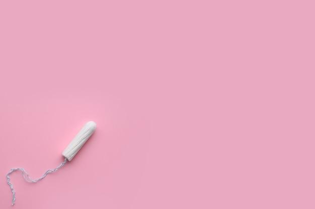 ピンクの背景に月経タンポン。衛生と保護。
