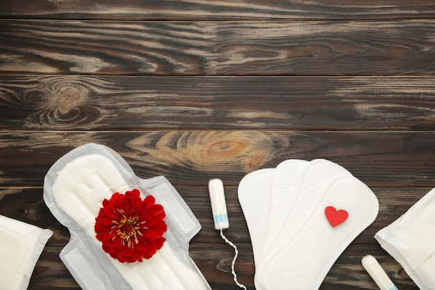 갈색 배경에 생리 탐폰과 패드입니다. 장미 꽃은 생리대에 놓여 있습니다. 월경주기. 위생 및 보호. 평면도. 세로 사진