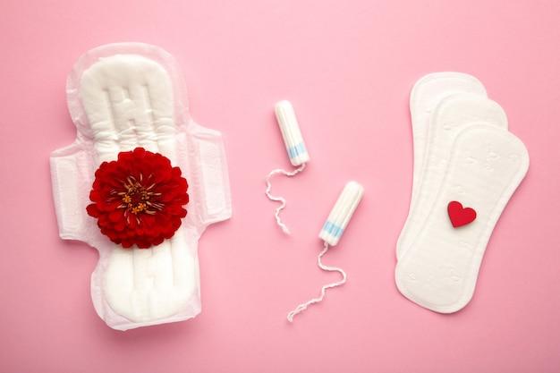 분홍색 배경에 생리용 탐폰과 패드. 장미 꽃은 생리대에 놓여 있습니다. 월경주기. 위생 및 보호. 평면도. 세로 사진
