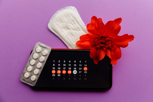Menstruation app calendar in smartphone with sanitary pad, pills and red flower on a lilac wall. woman critical days and hygiene protection concept.