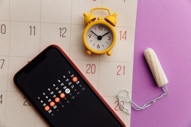 면 탐폰과 노란색 알람 시계가있는 스마트 폰의 월경 앱. 여성 중요한 일 및 위생 보호 개념.