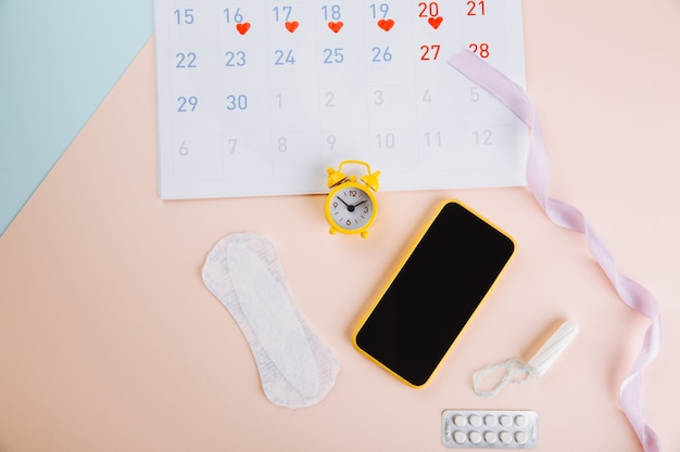 월경 달력 및 스마트 폰면 탐폰, 위생 패드 및 파란색 분홍색 배경에 노란색 알람 시계. 여성 중요한 날, 여성 위생 보호
