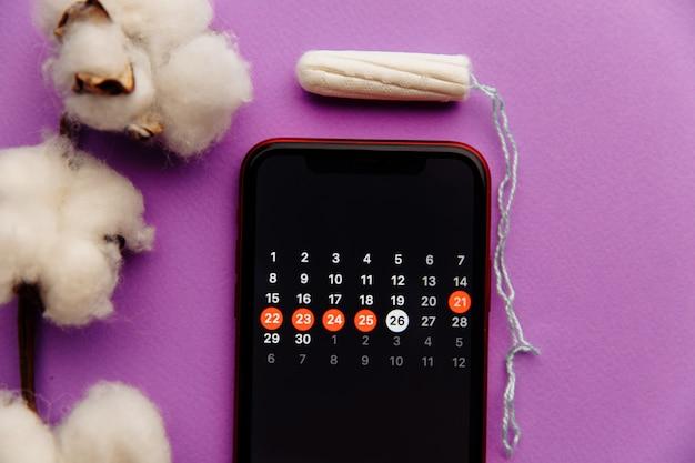 綿とタンポンを使ったスマートフォンの月経カレンダー。女性の重要な日と衛生保護の概念
