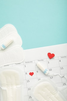 Menstruation calendar with cotton tampons and pads on blue background. woman critical days, woman hygiene protection. menstrual pain
