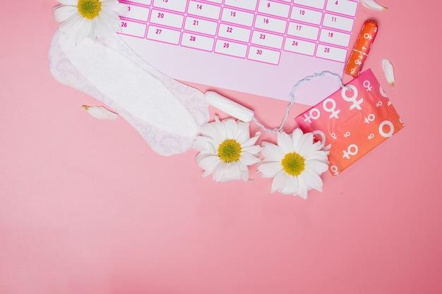 면 탐폰, 생리대, 흰 꽃이 있는 생리 달력. 여성의 중요한 날, 여성 위생 보호
