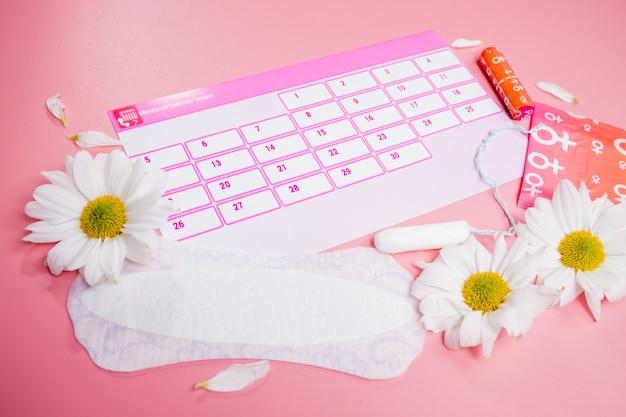 면 탐폰, 생리대, 흰 꽃이 있는 생리 달력. 여성의 중요한 날, 여성 위생 보호.