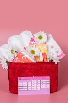 면 탐폰, 생리대, 흰 꽃이 있는 생리 달력. 여성의 중요한 날, 여성 위생 보호. 프리미엄 사진