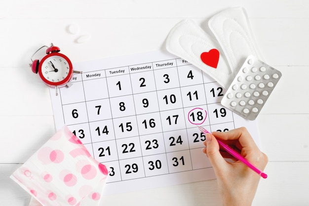 Menstruation calendar with pads, alarm clock, hormonal contraceptive pills. female's menstrual cycle concept. pain relievers for menstrual pain