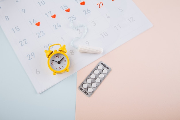 Menstruation calendar with yellow alarm, cotton tampon and contraceptive pills on pink background. woman critical days, woman hygiene protection concept.