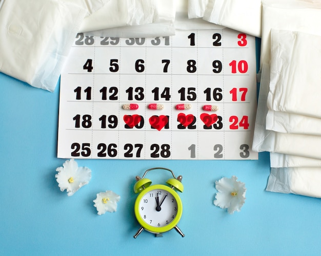 Menstruation cycle concept. menstruation calendar with sanitary pads, contraceptive pills, flowers and alarm clock.