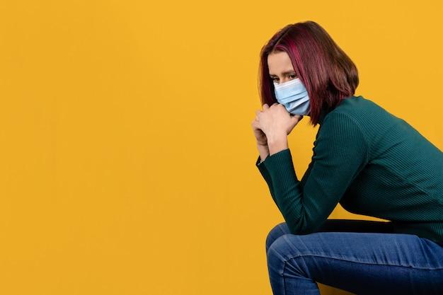 Covid-19 동안 정신 건강 및 대처. 노란색 배경에 얼굴 수술용 마스크를 쓴 걱정스러운 젊은 여성. 우울감을 느끼는 불안한 여자.