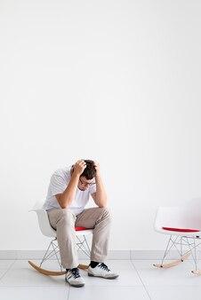 정신 건강 및 건강 관리. 머리를 잡고 의자에 앉아 두통을 가진 우울한 젊은이