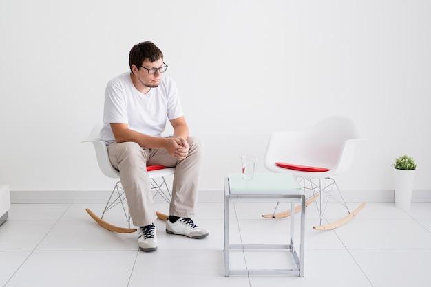 정신 건강 및 건강 관리. 의자에 앉아 두통을 가진 젊은 우울한 남자