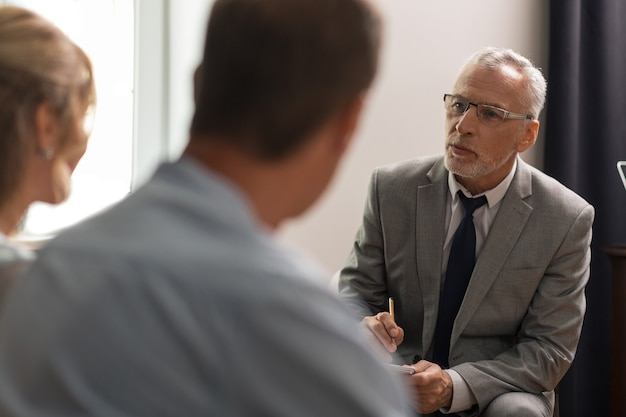 Mental health assessment. serious concentrated psychoanalyst in eyeglasses sitting in his office in front of his patients while assessing their mental health