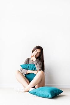 メンタルヘルスの概念。茶色のシャツと黒い革のショートパンツで床に座って枕を深く考えて美しい悲しい女性