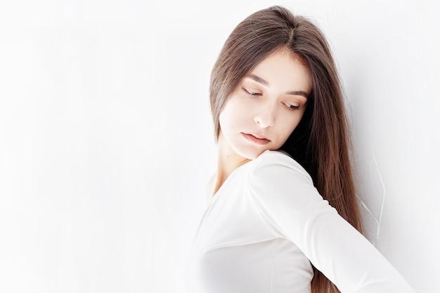 정신 건강 개념. 멀리보고 벽에 혼자 서있는 젊은 슬픈 여자