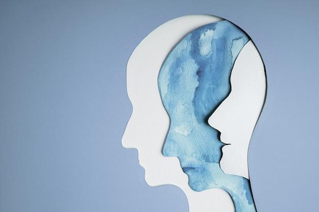 정신 건강 장애 개념. 양극성 장애 사람. 불안정한 사이코. 인간의 머리로 자른 종이 레이어는 다양한 감정을 표현합니다. 내부의 행복과 우울증 감정