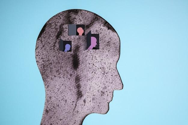 Концепция расстройства психического здоровья. слабый, подавленный подавленный человек. негативное настроение и чувства. слои вырезанной из бумаги головы человека, представляющие психологию депрессии и эмоций внутри