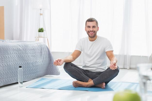 メンタルヘルス。ヨガマットの上に座って瞑想する素敵な陽気な男