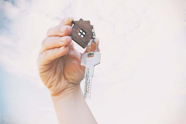 The mental key from door with wooden trinket in shape of house in woman's hand in front of sky