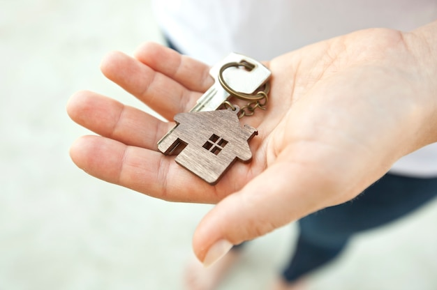 The mental key from door with wooden trinket in shape of house in woman's hand