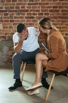 젊은 여성 의사와 이야기하는 정신 문제 남자는 검진 의료 상담에서 환자를 돕습니다