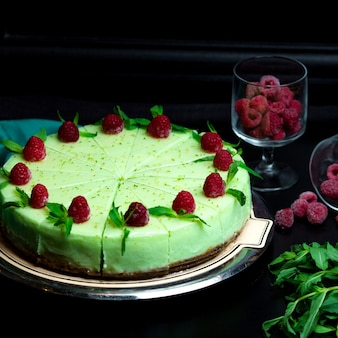 Menthol cheesecake with mint leaves on it and raspberries
