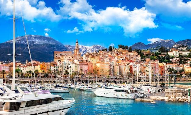Ментон, красивый город на юге франции. вид на море с парусными лодками и разноцветными домами