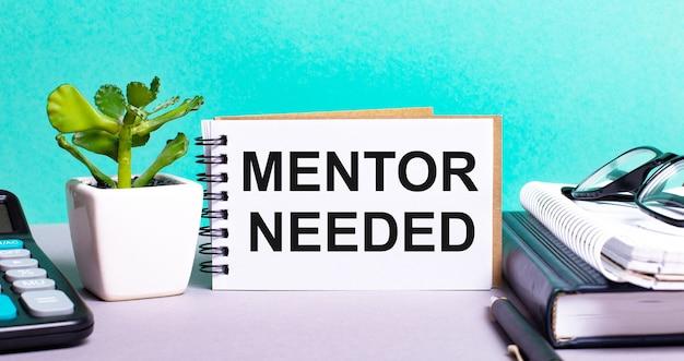 Mentor neededは、鉢植えの花、日記、電卓の横にある白いカードに書かれています。組織の概念。