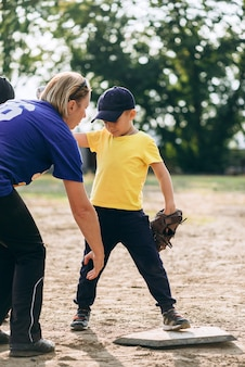 Mentor shows the little boy how to stand properly while playing baseball