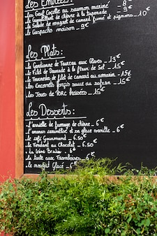 Menu board on the outside wall of a restaurant in Paris.