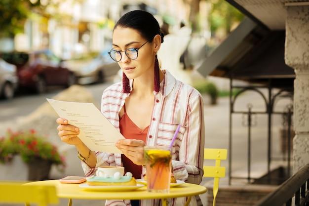 メニュー。人気カフェのサマーテラスに座りながら、メガネをかけてメニューを眺める落ち着いた気配りのある女性